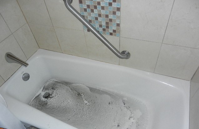 A bathtub backed up with dirty water