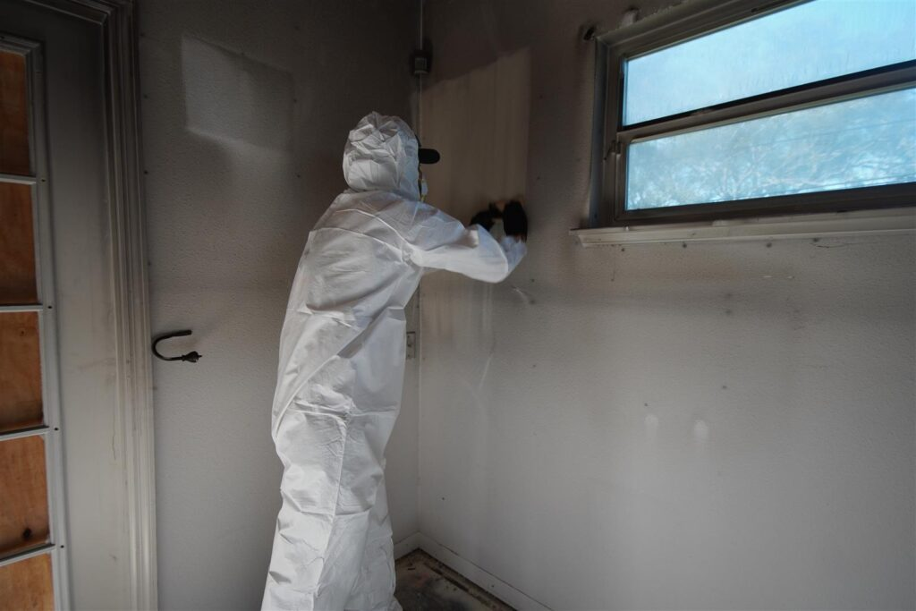 Worker cleaning soot off of walls