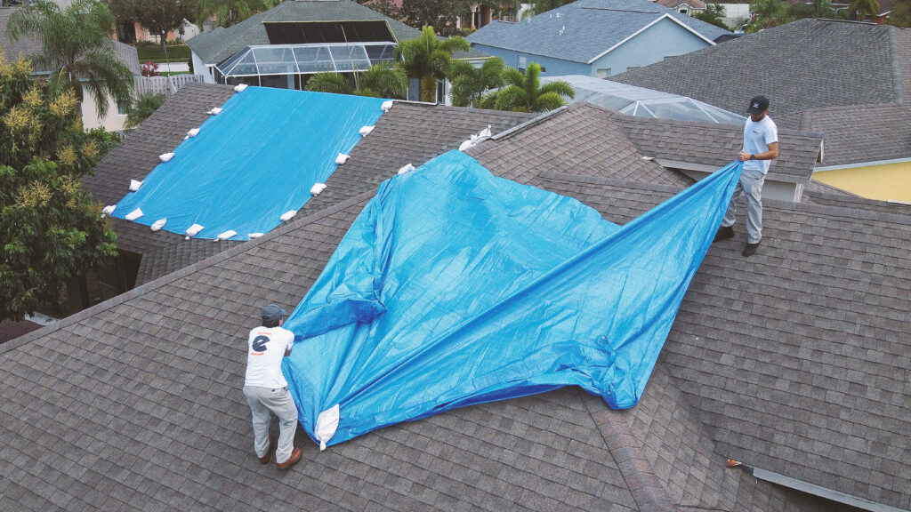 Workers putting a tarp on a roof to prevent water damage from rain