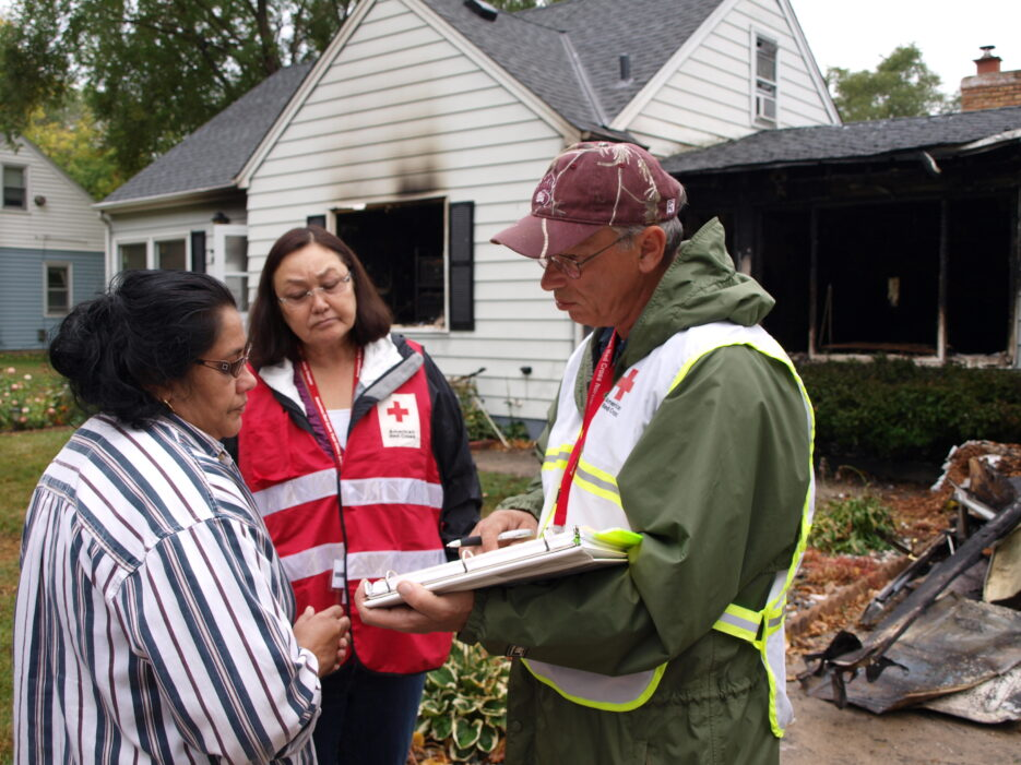 Red Cross Volunteers helping a house fire victim